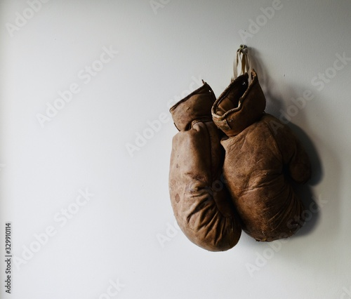 Pair of old and worn boxing gloves hang on the wall Wallpaper Mural