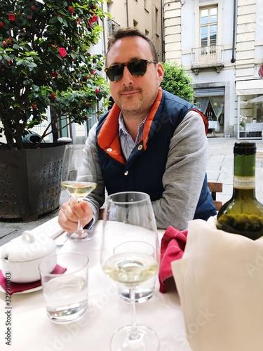 Obraz Portrait Of Man Having Wine While Sitting At Sidewalk Cafe - fototapety do salonu