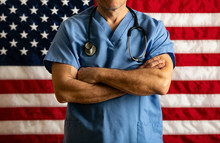 Health: Doctor With Arms Crossed In Front Of Flag