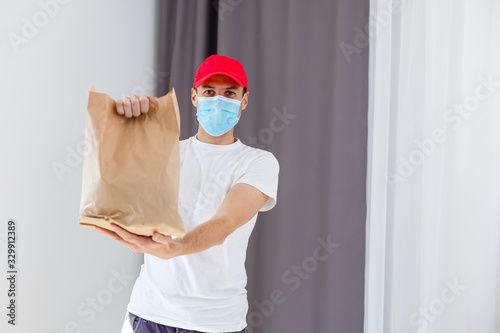 obraz PCV Delivery man holding paper bag with food on white background, food delivery man in protective mask