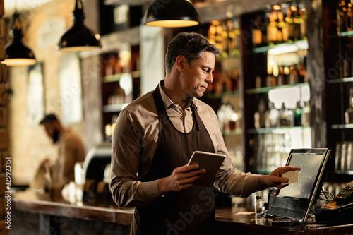 Smiling bartender at cash register working in a pub. Wallpaper Mural