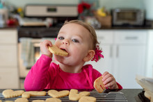 Closeup Of Little Girl Taking A Bite Out Of A Heart Shaped Sugar Cookie