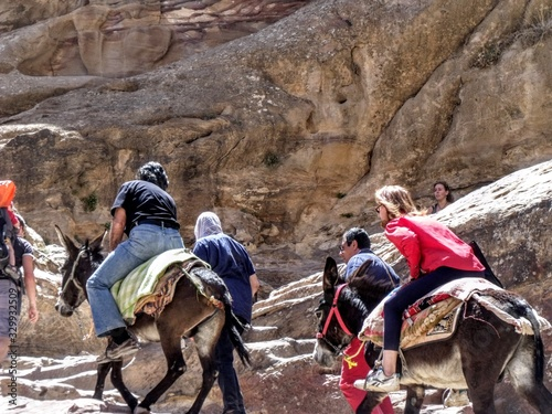 Fototapeta People Riding Donkey While Climbing By Rock Formation