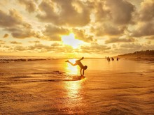 Silhouette Man Practicing Handstand At Beach Against Cloudy Sky