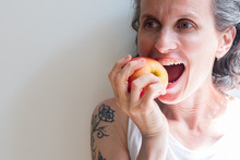 Close-up Of Mature Woman Eating Apple Against White Wall