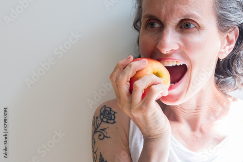 Obraz Close-up Of Mature Woman Eating Apple Against White Wall - fototapety do salonu