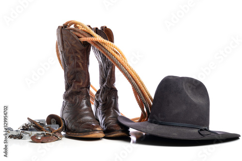 Photo Western boots and a lap or lariat rope and spurs and a cowboy hat on a white bac