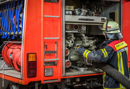 Obraz na plátne Firefighter Attaching Hose To Machinery