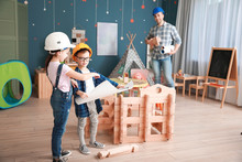 Father And Little Children Dressed As Builders Playing With Take-apart House At Home
