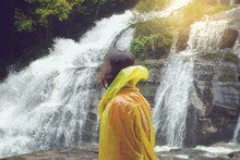 Side View Of Woman In Raincoat Standing Against Waterfall