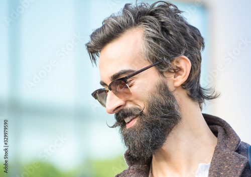 Fototapeta Close-up Of Smiling Hipster Man Wearing Sunglasses Against Building
