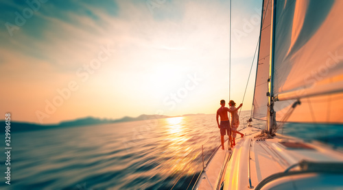 Young couple enjoys sailing in the tropical sea at sunset on their yacht Obraz na płótnie
