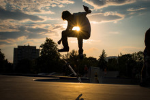 Silhouette Man Jumping While Skateboarding In Park Against Sky During Sunset
