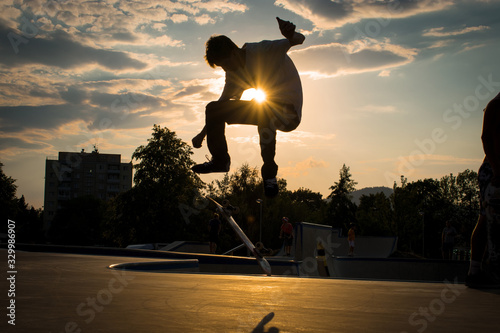 Silhouette Man Jumping While Skateboarding In Park Against Sky During Sunset - fototapety na wymiar