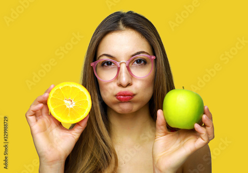 Papel de parede Young Woman Holding Orange And Granny Smith Apple Against Yellow Background