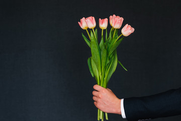 man's hand giving bouquet of pink tulips