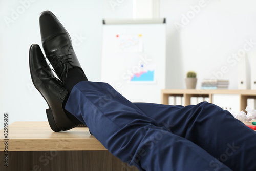 Fotografie, Tablou Lazy office employee resting with feet up on desk at workplace, closeup