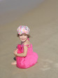 Portrait Of Little Girl Sitting On Sand At Beach