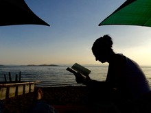 Silhouette Woman Reading Book At Beach