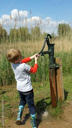Fotografiet Boy Fetching Water Using Hand Pump