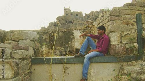 Photo Man Sitting On Wall At Golconda Fort