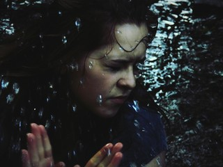 Close-up Of Woman In Lake With Eyes Closed While Water Splashing On Her Face