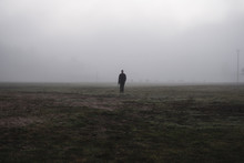 Full Length Of Man Standing On Landscape Against Sky During Foggy Weather