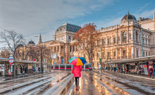 Woman In Red Clothes With Multicolored Umbrella - Tram Moving On A Street  - View Of The University Of Vienna (Universitat Wien) - Austria