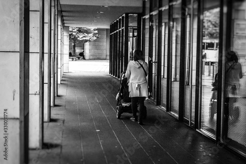 Obraz Rear View Of Woman Walking With Baby Carriage On Colonnade - fototapety do salonu