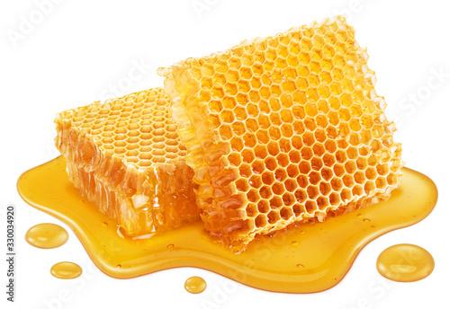 Stampa su Tela Honeycombs and sweet sticky honey puddle isolated on white background