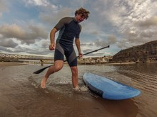 Man Standing By Paddle Board On Beach