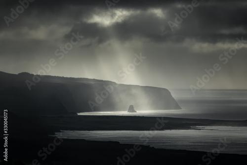 Fotografie, Obraz Darkness over islet boulder in the coastline