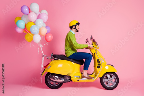 Obraz Profile side view of his he nice attractive cheerful cheery glad guy driving moped bringing carrying bunch air balls festive decoration isolated over pink pastel color background - fototapety do salonu