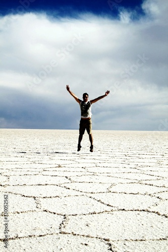 Fototapety, obrazy: Full Length Of Man With Arms Outstretched At Salar De Uyuni Against Sky