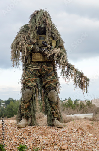 Fototapeta Army Man In Ghillie Suit With Rifle Standing On Field
