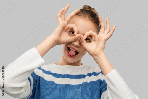 people concept - funny teenage girl looking through finger glasses over grey bac фототапет