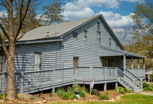 Photo An old grey wood siding house with a wheelchair accessible ramp