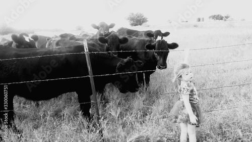 Photo Girl Standing Against Cows On Field At Farm