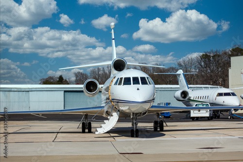 Two luxury private jets on the tarmac by hangers at a regional airport Canvas Print