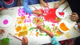 High Angle View Of People Painting In Paper On Table