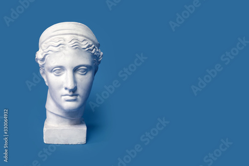 Fotografiet Marble head of young woman, ancient Greek goddess bust isolated on pink background