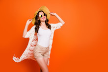 Photo Of Amazing Lady Summer Time Walking Hot Ocean Sand Tropical Resort Enjoy Breeze Wear Sun Hat Specs Trendy Lace Beach Cloak Shorts Tank-top Isolated Orange Background