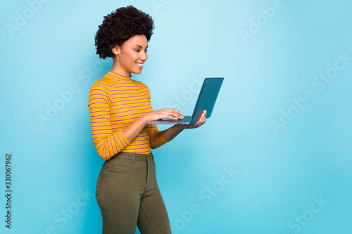 Obraz Profile photo of pretty dark skin wavy lady hold notebook hands reading broker service website want to buy apartments wear yellow striped jumper isolated blue color background - fototapety do salonu