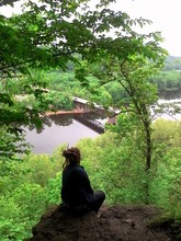 High Angle View Of Woman Sitting On Cliff Against Lake
