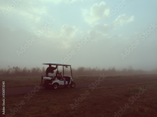 Obraz na plátně Father With Son In Golf Cart On Road Amidst Field During Foggy Weather