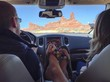 Cropped Image Of Family Sitting In Car Against Rock Formation