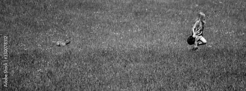 Fotografía Panoramic View Of Girl And Dog Running On Grassy Field