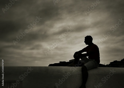 Fototapety, obrazy: Silhouette Man Sitting On Retaining Wall Against Cloudy Sky