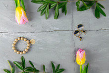 Jewelry, Bracelet With Keychain And Gold Earrings Together With Tulips And Green Laid On A Concrete Background. Inside The Composition, Free Space