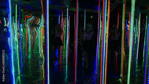 Obraz Woman Photographing In Illuminated House Of Mirrors - fototapety do salonu